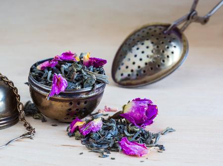 Tea strainer closeup, tea leaves and rose buds, selective focus