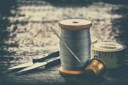 Creative image of sewing accessories for needlework sewing, hobby, retro style on an old wooden surface Archivio Fotografico