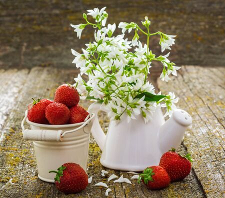 seasonally: Beautiful still life of fresh red strawberries in a decorative bucket on an old wooden surface. A bouquet of white flowers in a porcelain vase