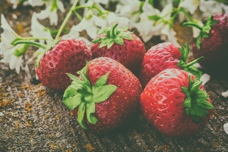 Beautiful bouquet of fresh red strawberries on an old wooden surface, retro style Stock Photo