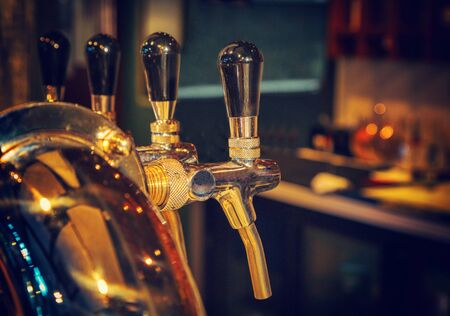 Chromed taps for draft beer in a modern bar. Detail of beer machine, beer dispenser, close-up, selective focus, retro style