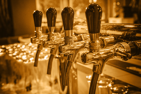 Chromed taps for draft beer in a modern bar. Detail of beer machine, beer dispenser, close-up, selective focus, retro style, toning
