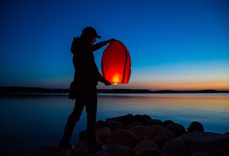man launches a Chinese orange heavenly flying lantern with a candle in the night sky, tradition, make a wish Imagens