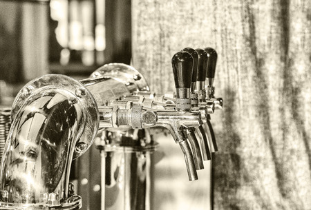 Chromed taps for draft beer in a modern bar. Beer machine detail, beer dispenser, close-up, selective focus, retro style, black and white