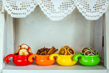 Assortment of dried fruits, spices and spices in colored cups closeup on white wooden background, healthy food, Stock Photo