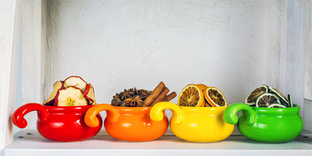 assortment of dried fruits, spices and spices in colored cups close-up on white wooden background, healthy food