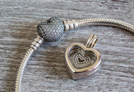 Jewelry for women silver bracelet and heart symbol pendant, modern fashion, amulets, precious products, macro, retro style, selective focus