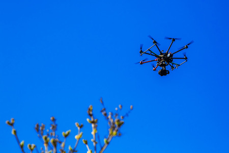 quadrocopter with a camera flying in a blue sky controlled by a wireless remote control, digital hum, aeronautics