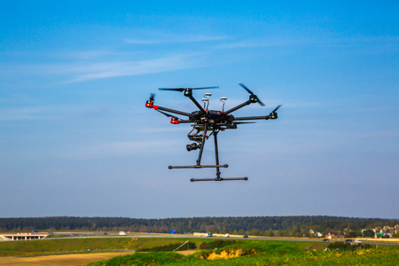 quadrocopter with camera flying over beautiful scenery and blue sky controlled by wireless remote control, digital hum, aeronautics Stock Photo