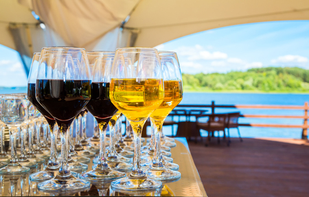 creative image, festive wine glasses with red and white wine on a table on a blue sky background. view of the lake. celebration, holiday. selective focus Reklamní fotografie