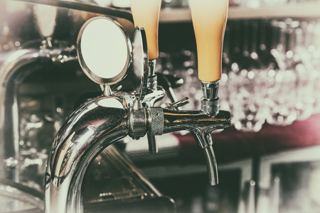 Chromed taps for draft beer in a modern bar. Beer machine detail, beer dispenser, close-up, selective focus, retro style Фото со стока