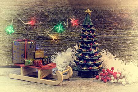 creative image Christmas tree and gift boxes sleigh with gifts on an old wooden surface, place for text, retro style