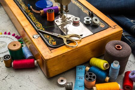 Sewing machine and accessories for sewing, scissors, needles and tailor meter on the table. The concept of sewing accessories.