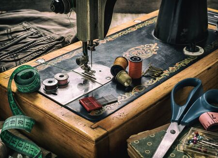 Old sewing machine and accessories for sewing, scissors, needles and tailor tape on the table. The concept of sewing accessories. Retro toning