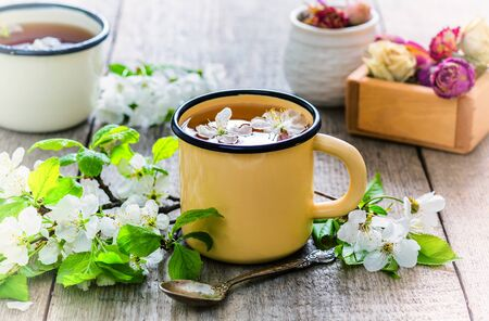 Healthy floral tea made from apple tree flowers in a metal mug. Therapeutic drink. Fragrant. Drug. Retro style.