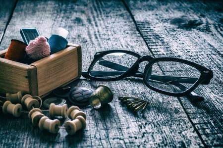 The concept of sewing accessories. Sewing tools and accessories for sewing threads, spools, scissors, buttons, needles, pin and tailor meter on an old wooden surface. Retro style.