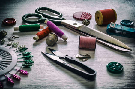 Various accessories for needlework. A set of sewing supplies for fabrics and spools of thread, scissors and a thimble. Retro toning Banque d'images