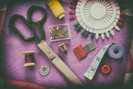 A set of sewing accessories. Sewing accessories for sewing: lilac fabric, thimbles, spools of thread, tailor's scissors, a set of pins and a tape measure on a gray wooden table. View from above. Retro style