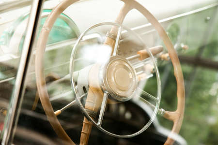 aged: Retro car steering wheel through the glass Stock Photo