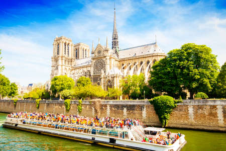 PARIS, FRANCE - 19 May 2018: Notre Dame Cathedral church and river boat cruise Editorial