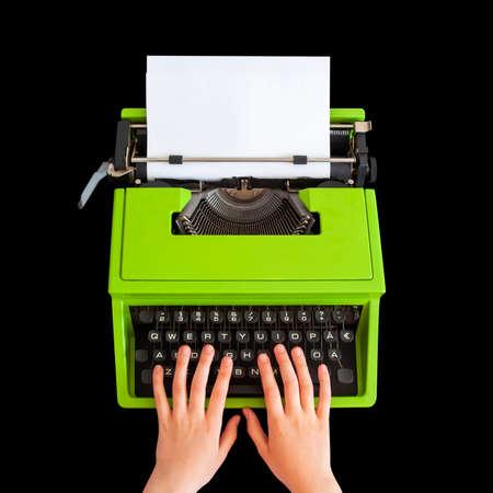Hands typing on retro typewriter over black background Archivio Fotografico