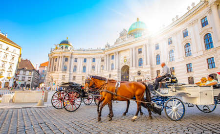 Vienna, Austria - 10 September, 2021: Hofburg palace and horse carriage on sunny Wien street 에디토리얼