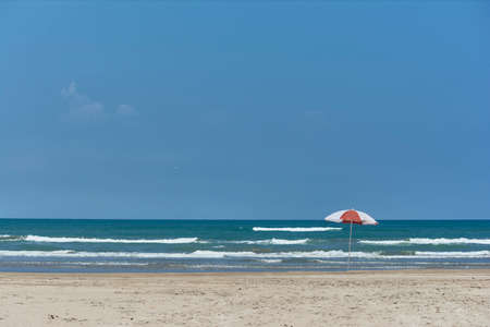 Umbrella and sunbed at the beach landscape with a great blue sky