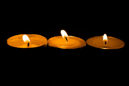 Candles, burning scented candles on a black background for any purpose Stock Photo