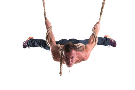 The man hanging on the ropes with a strained expression on his face isolated on white background for any purpose