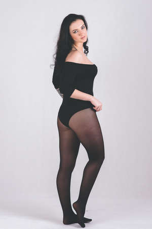 Full girl in black bodysuit stands, on light background for any purpose Stockfoto