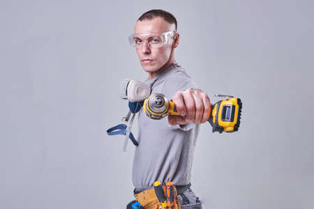 Master Builder-finisher in work clothes, with a drill screwdriver in hand for any purpose Banque d'images