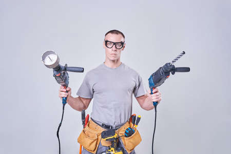 Master-Builder-finisher in their working clothes, with two hammers in his hands for any purpose