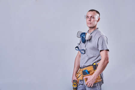 Master Builder-finisher in work clothes, with a drill screwdriver in hand for any purpose Stock Photo
