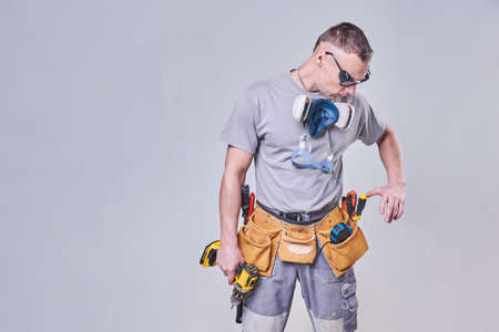 Master Builder-finisher in work clothes, with a drill screwdriver in hand for any purpose Archivio Fotografico