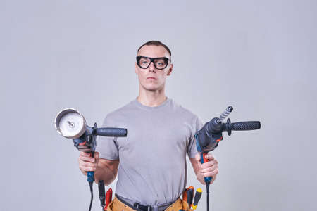 Master-Builder-finisher in their working clothes, with two drill machine in his hands for any purpose Stock Photo