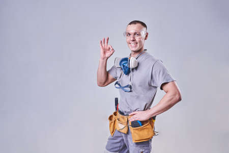 Master Builder-finisher in working clothes, shows the sign OK for any purpose Фото со стока