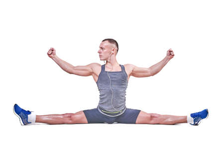 Beautiful man performs side splits in sportswear isolated on a white background for any purpose