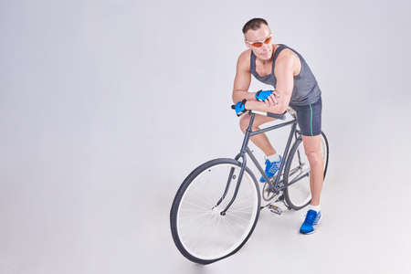 A handsome sports man sits on a Bicycle for any purpose Foto de archivo