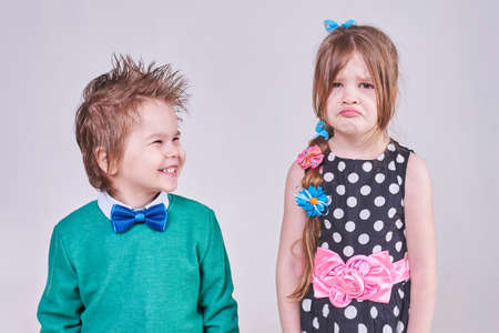 A handsome little boy, wearing a blue bow tie and a green sweater, laughs at a crying girl for any purpose