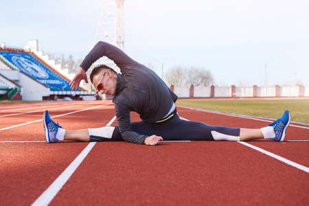 A man sportsman performs a transverse twine, on the athletics track of the stadium. For any purpose Zdjęcie Seryjne