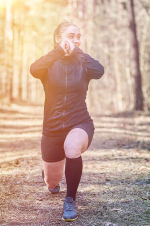 Sports girl does the squats in the woods for any purpose