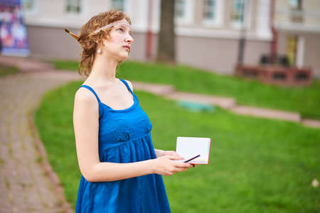 Beautiful girl-artist on the street in a blue dress writing something in a notebookl for any purpose
