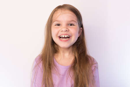 Little cute girl with a satisfied expression on his face, smiling widely on a light background for any purpose