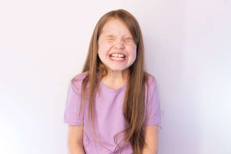 The lovely little girl, in a lilac undershirt and with a flowing hair, having strongly blinked, shows teeth, on a light background for any purpose
