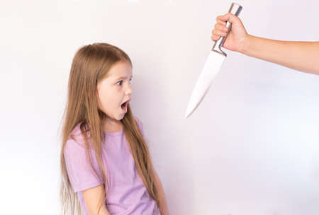 The little girl, frightened looks on the knife that it swung on a light background for any purpose