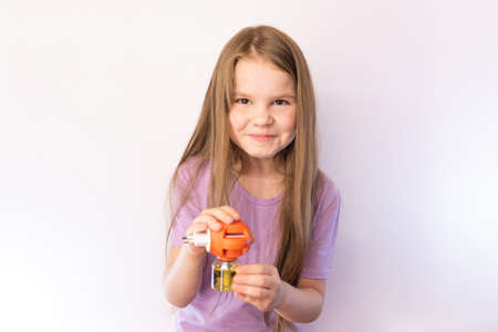 Little girl holding a fumigator from mosquitoes and smiling on light background for any purpose