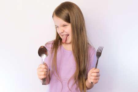 Niña linda sosteniendo una cuchara y un tenedor con disgusto sacando la lengua y haciendo una mueca contra un fondo brillante para cualquier propósito