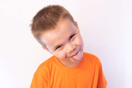A little boy shows tongue with a cheerful expression on his face, on a light background for any purpose