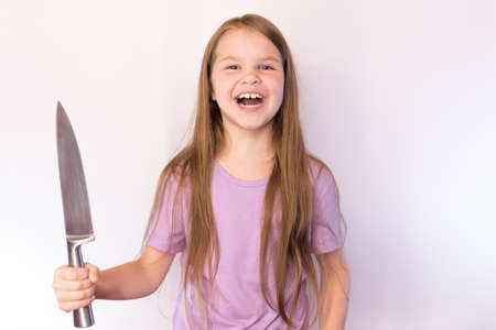 A little girl with a large kitchen knife, in a lavender shirt and with her hair, laughs evilly, on a light background for any purpose Archivio Fotografico