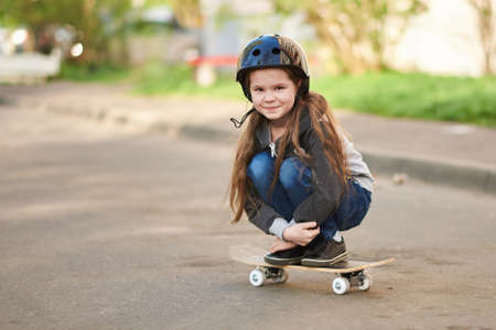 A little girl squats on a skateboard. For any purpose
